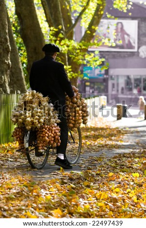 French Man riding down leafy garden path on bicycle loaded with onions and garlic