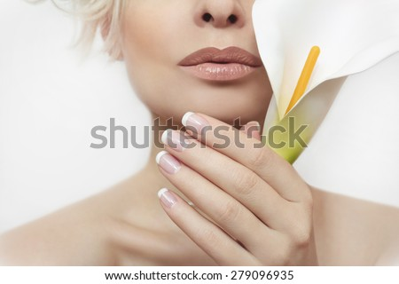 French manicure for the girl with the flower in her hand on a light gray background. - stock photo