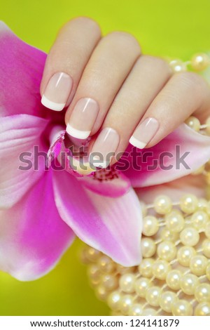 French manicure on a green background with an Orchid and pearls. - stock photo