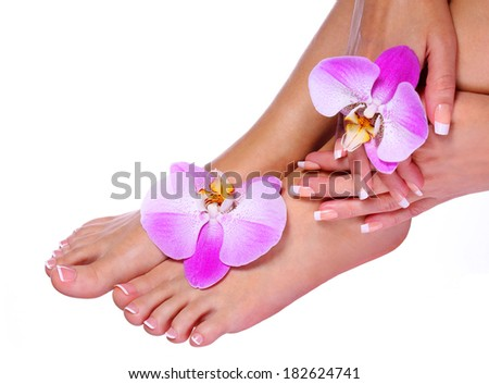 French Manicure on Beautiful Female Feet and Hands with pink orchid flowers isolated on white. Nail care. Pedicure. Spa - stock photo