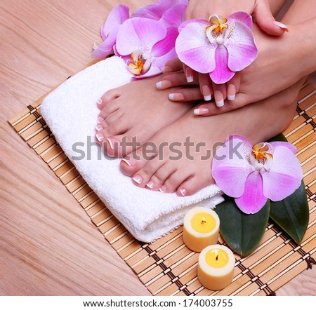 French Manicure on Beautiful Female Feet and Hands with pink orchid flowers on bamboo mat. Nail care. Pedicure. Spa Salon - stock photo
