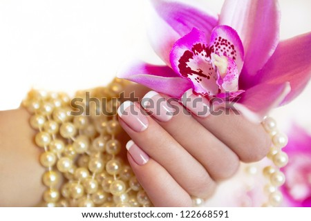 French manicure to a woman's hand with an Orchid and beads. - stock photo