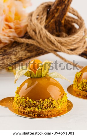 French mousse cake covered with caramel glaze decorated with physalis. Modern european cake pastry. Shallow focus