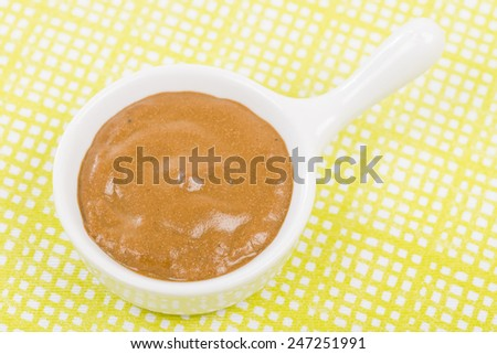 French Mustard - Bowl of french mustard on a green background. - stock photo