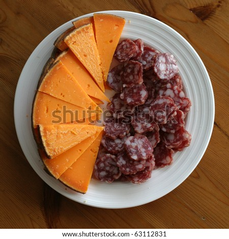 French old mimolette cheese and hard smoked sausage on a plate - stock photo