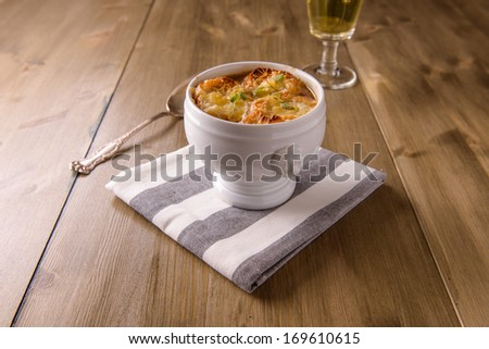 French onion soup on a wood table with a glass of white wine - stock photo