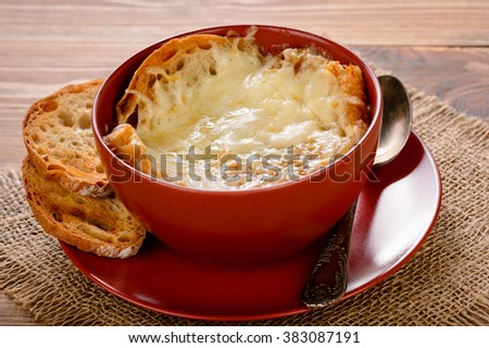 French onion soup with toasts on wooden table. - stock photo