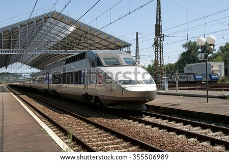 FRENCH PASSENGER TRAIN DEPARTING  PAU STATION IN SOUTHERN FRANCE - CIRCA 2013 - A TGV fast train departing Pau railroad Station in southwest France - stock photo