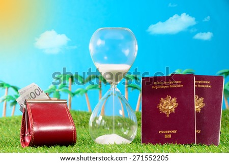 french passports and hourglass to the holidays on grass - stock photo