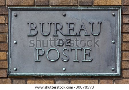 French post office sign made of brass and bolted on a brick wall - stock photo