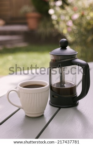 French Press and White Espresso Cup in a bright outdoor setting.  - stock photo