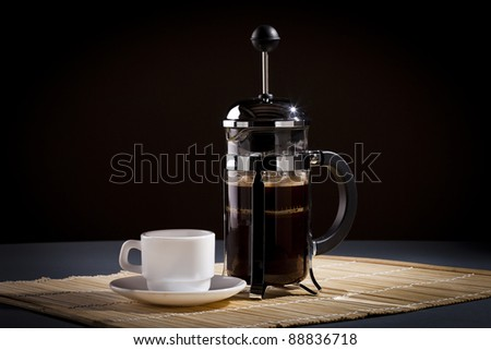 French press coffee maker and coffee cup studio lit on table with dark background - stock photo