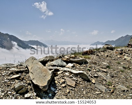 French Pyrenees mountains range in fog  with big stone on the foreground HDR processed - stock photo