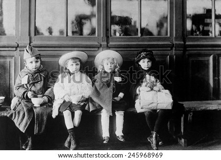 French refugee children during WWI. While waiting for train, children were fed with bread and milk from American Red Cross soldiers canteen. 1917-1918.