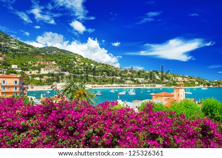 french reviera, view of luxury resort and bay of Villefranche-sur-Mer near Nice and Monaco. seafront landscape with azalea flowers - stock photo