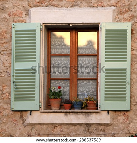 French rustic window with green wood shutters and flower pot in stone rural house, Provence, France. Square image, sunset light - stock photo