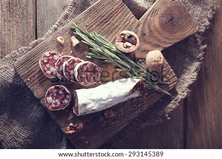 French salami on cutting board on wooden table - stock photo