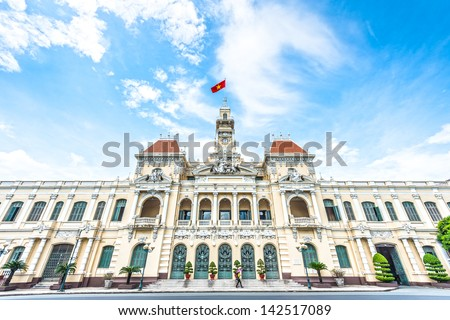 French style of building in Vietnam, Asia. Beautiful Ho Chi Minh City Hall. Facade of house with ornate design. Red flag contrasts with blue sky and clouds. Tourist attraction, famous landmark.