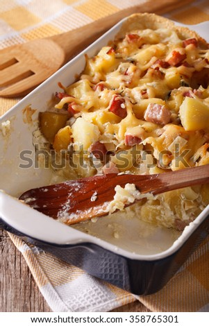 French tartiflette potatoes with bacon and cheese close up in baking dish. vertical - stock photo