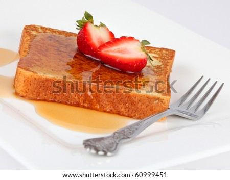 French toast and syrup with strawberries isolated on white with fork. - stock photo