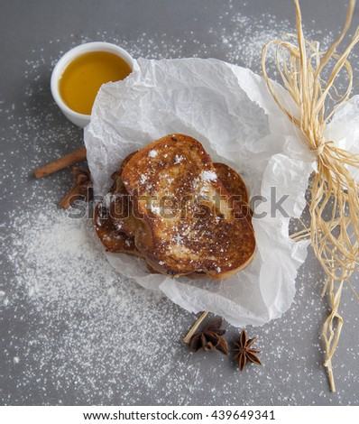 French toast served with honey and anise.Studio shot on a gray stone table. - stock photo
