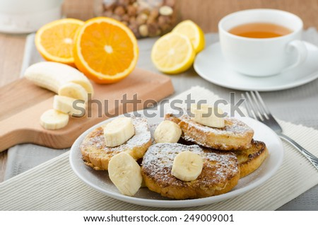 French toast to sweet, with banana sprinkled with sugar, fresh tea, breakfast - stock photo