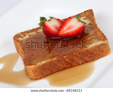 French toast with syrup and strawberry on a white plate - stock photo