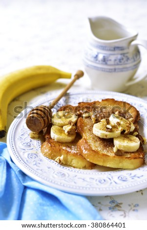 French toasts with banana,walnuts and cinnamon for a breakfast. - stock photo