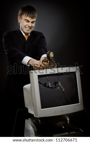 frenzy businessman chop-down old monitor on dark grey background