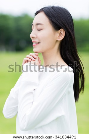 fresh air in the park, there is a beautiful chinese girl praying in silence