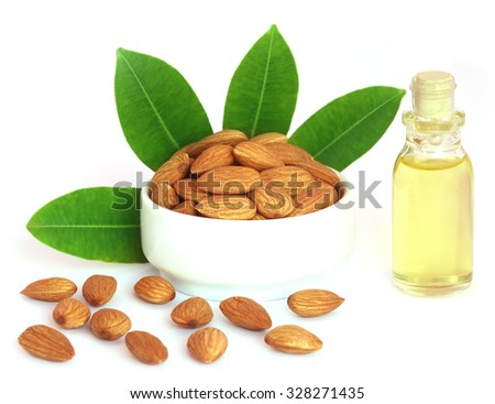 Fresh almonds with oil over white background - stock photo