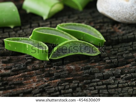 Fresh aloe vera slice on black wooden background.