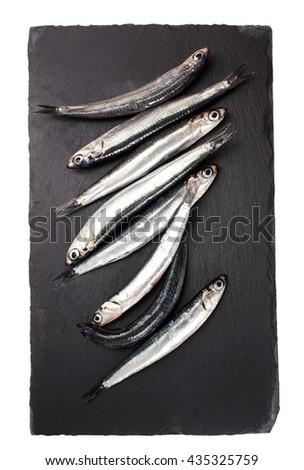 fresh anchovies over slate plate isolated on white