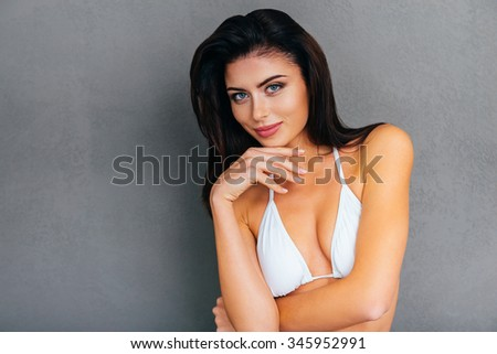 Fresh and beautiful. Attractive young smiling woman in white bikini holding hand on chin and looking at camera while standing against grey background