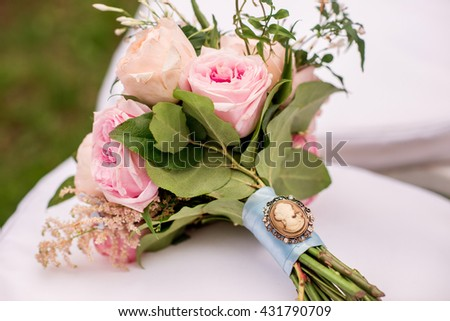 fresh and beautiful wedding bouquet with cameo on a white chair - stock photo