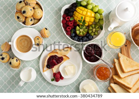 Fresh and bright continental breakfast table with fruit plate - stock photo