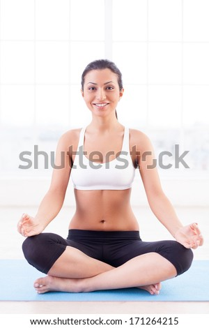 Fresh and calm. Beautiful young Indian woman sitting in lotus position and smiling at camera - stock photo