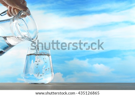 Fresh and clean drinking water being poured from jug into glass on sky background - stock photo