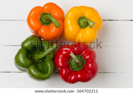 Fresh and colorful bell peppers on a white wooden background. - stock photo