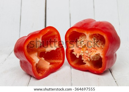 Fresh and colorful red bell pepper sliced on a white wooden background. - stock photo