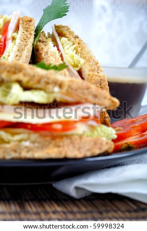fresh and delicious classic club sandwich over a black glass dish with coffee and vegetable - stock photo