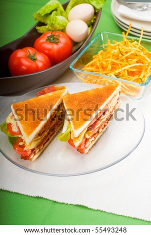 fresh and delicious classic club sandwich over a transparent glass dish - stock photo