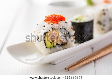 Fresh and delicious maki sushi with sake glass and chopsticks on a wooden white table. - stock photo