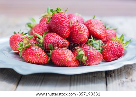 Fresh and delicious organic strawberries on old metal plate, on wooden table. Perfect for your healthy eating and dieting. Selective focus. Natural sunlight. - stock photo