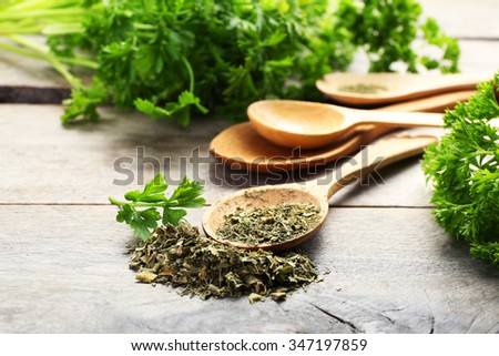 Fresh and dried parsley on wooden background