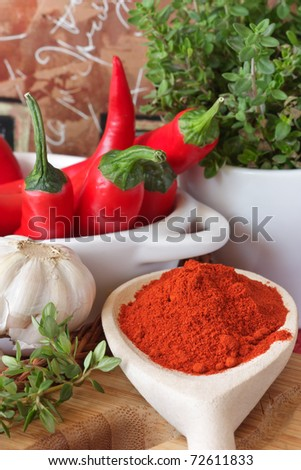 Fresh and dried red chili pepper on a wooden spoon. - stock photo