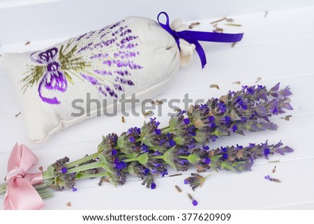 Fresh and dry flowers in pouch on white wooden table - stock photo