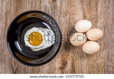 Fresh and fried eggs on wooden background - stock photo
