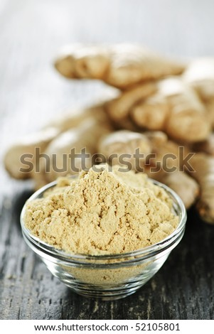 Fresh and ground ginger root spice on wooden table - stock photo