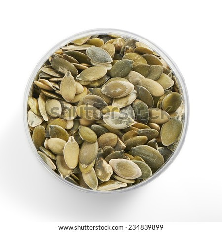 fresh and healthy superfood pumpkin seeds in a glass jar shot from above. on a white background with a soft shadow. - stock photo